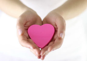 picture of two hands holding a pink heart